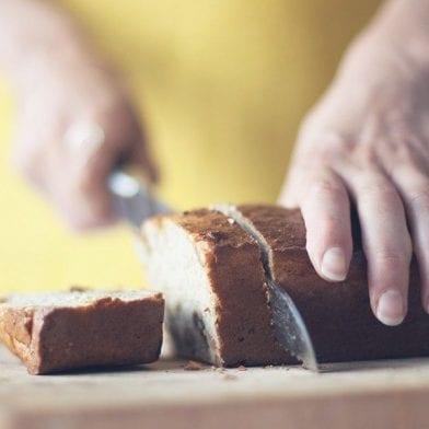 Woman slicing a fresh baked banana quark bread