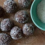 Homemade protein powerballs next to a bowl of coconut rasps